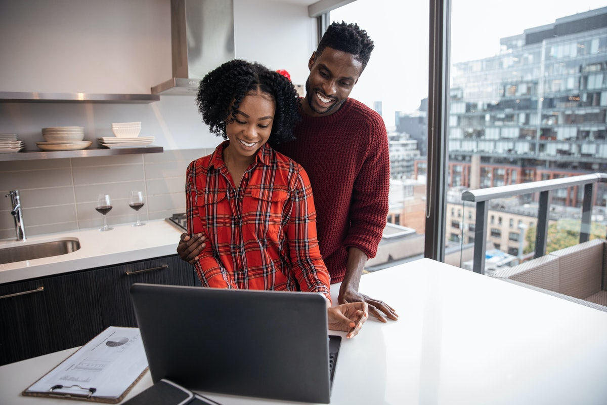 A happy couple looks at their laptop in their bright kitchen.