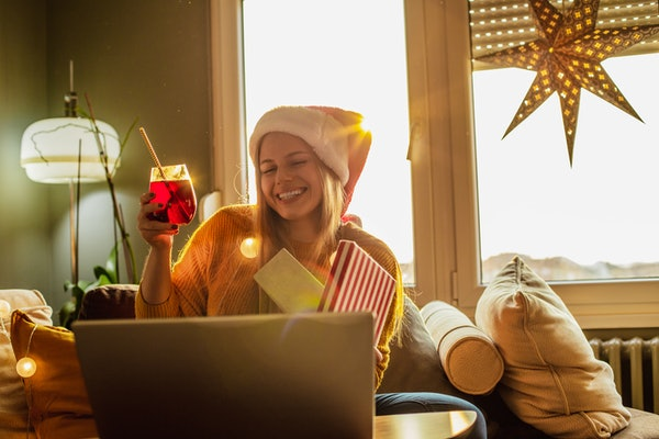 A young woman smiles while holding a present and participating in virtual Secret Santa with her best friends.