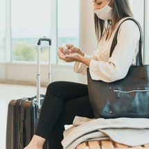 A woman wearing a mask sits at an airport and applies hand sanitizer. Traveling and taking vacations during the COVID-19 pandemic requires precautions.