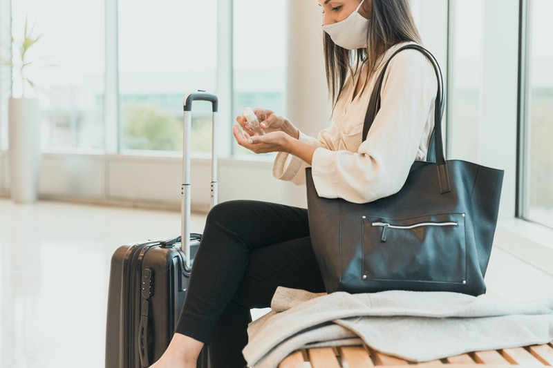 A woman wearing a mask sits at an airport and applies hand sanitizer. Traveling and taking vacations...