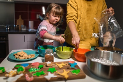 mom and kid baking holiday cookies