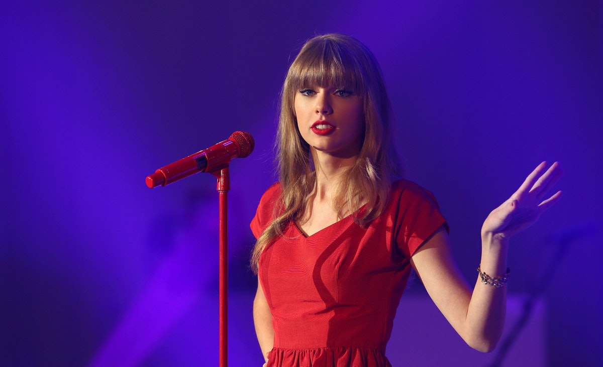 Taylor Swift performs at a Christmas concert in her red dress and matching microphone stand