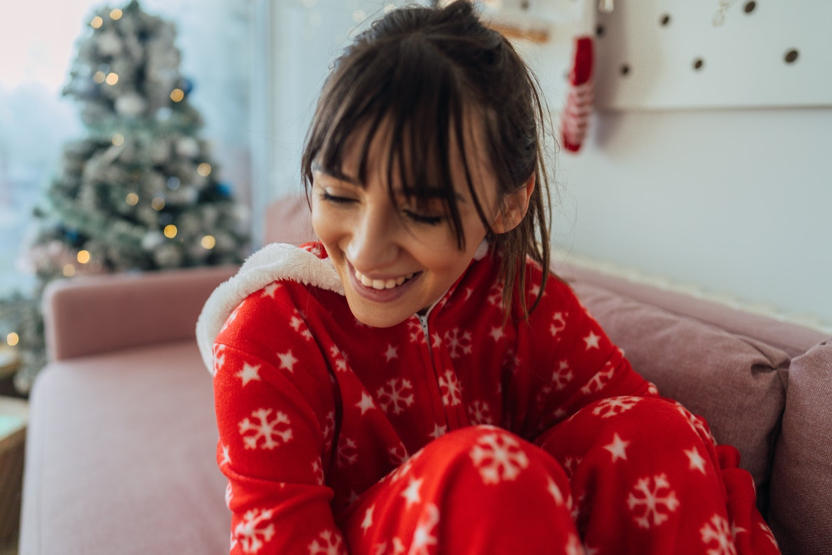 A happy woman in Christmas pajamas sits on her couch, next to her Christmas tree.