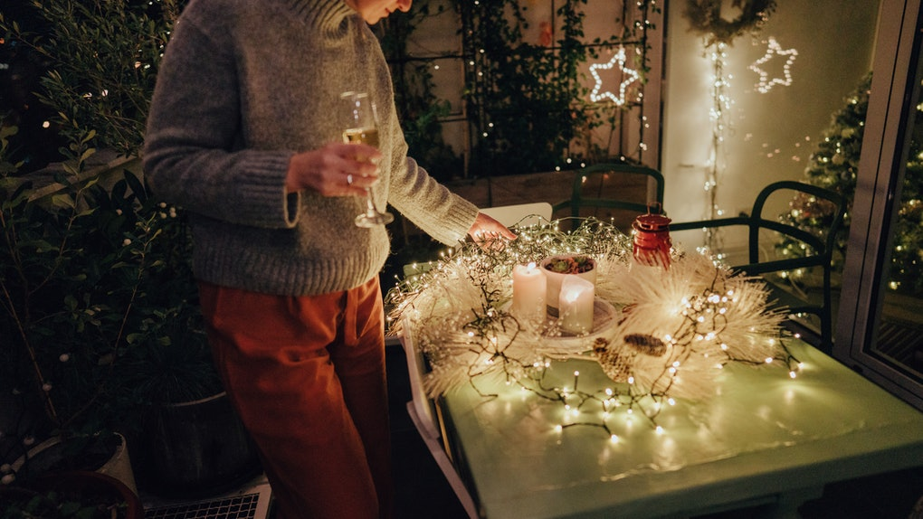 A woman looks down at her cozy candle table setup for Christmas.