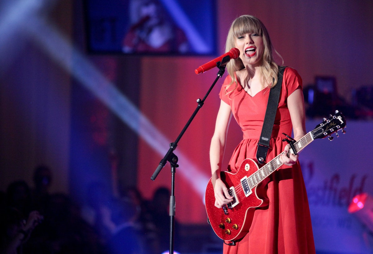 Taylor Swift plays her red guitar wearing her matching dress on stage for a Christmas concert