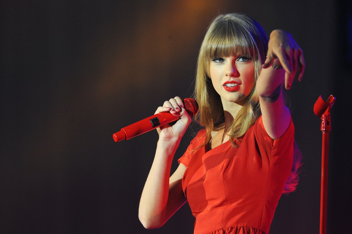 Taylor Swift performs a holiday concert in a red dress and matching microphone, complete with a her signature red lip