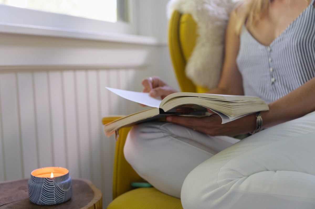 A girl reads by the candle lit, snuggled in a chair