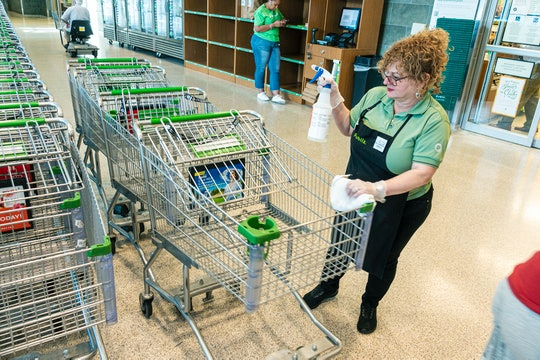 employee spraying carts at publix