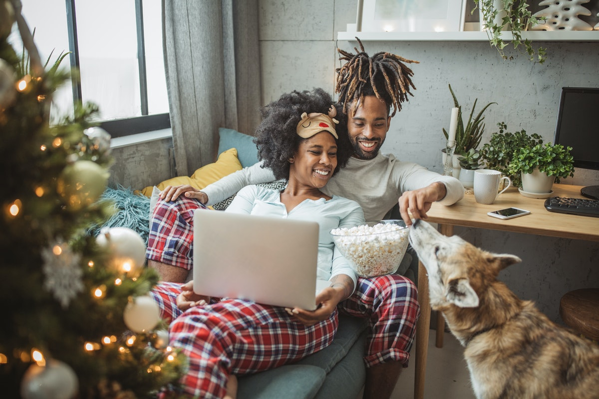 A happy couple relaxes in their holiday PJs on a couch.