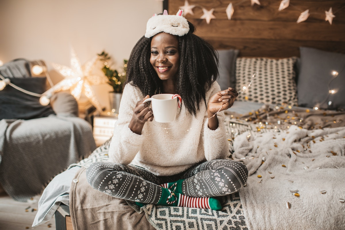 A woman in Christmas pajamas sits on her bed with twinkle lights and a mug of hot cocoa.