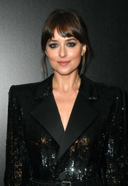 Dakota Johnson styles curtain bangs with side sweeping motions