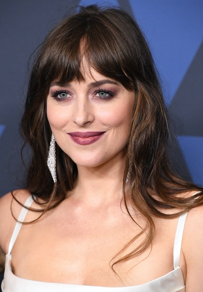 Dakota Johnson styles curtain bangs with volume and a slight middle part
