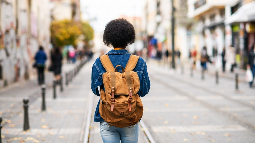 A woman walks a city street. Stress can hurt heart health in multiple ways, according to experts.