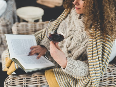 woman reading book and having a glass of wine