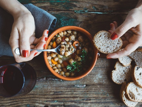 A woman eats a hearty vegan stew. What can going vegan do to your body?