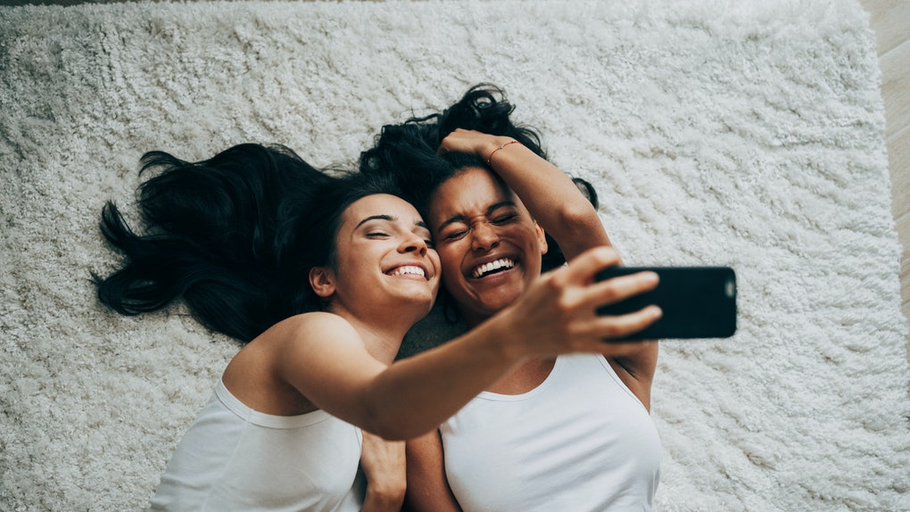 A couple laughs and takes a selfie while laying on a white carpet on the floor.