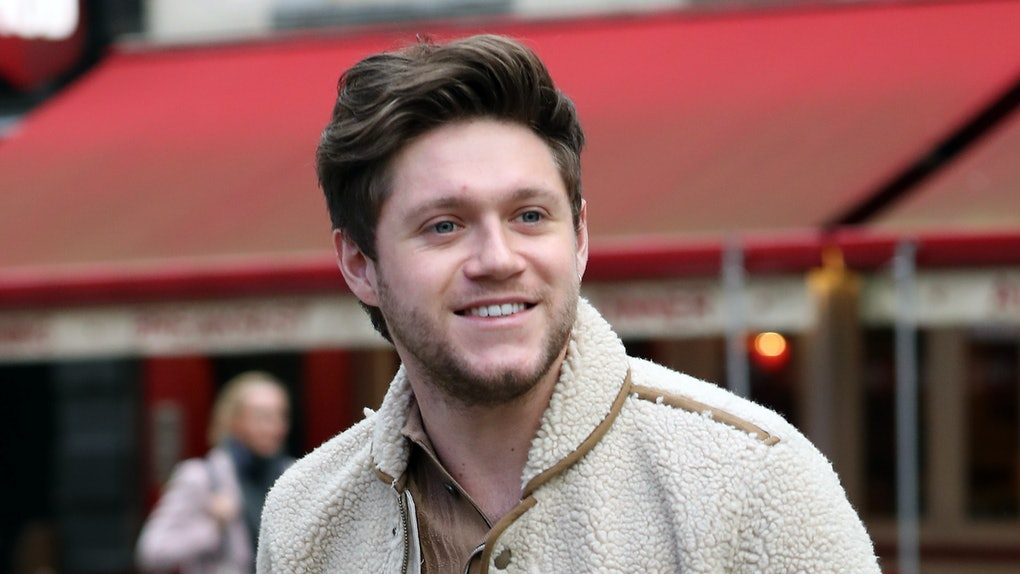 Niall Horan steps out in a cream-colored sweater and grey slacks.
