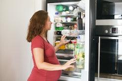 pregnant woman looking in fridge