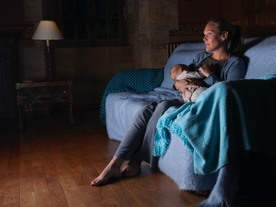 mom breastfeeding on a couch at night