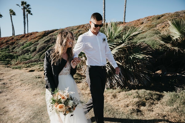 A young couple laughs in wedding attire after getting married in the desert.