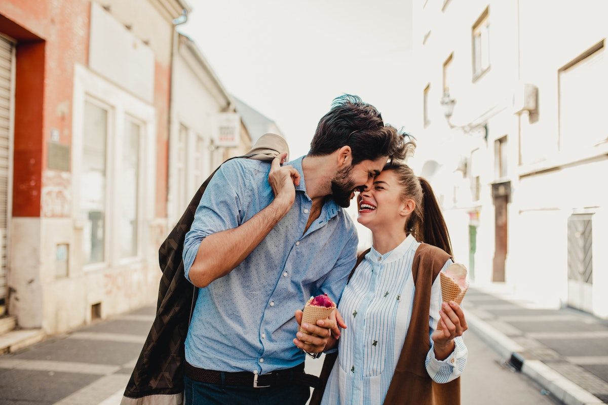 A couple shares a sweet moment while on a romantic trip and holding ice cream cones.