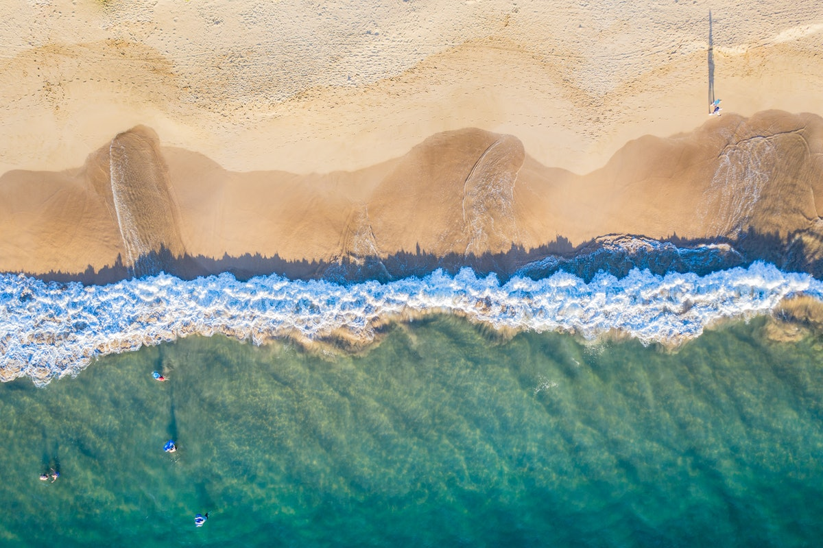 An aerial view of a beach in Maui, Hawaii shows teal water and bright sand.