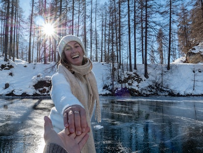 A happy women wearing a scarf, sweater, and beanie skates on an icy pond while holding her partner's...