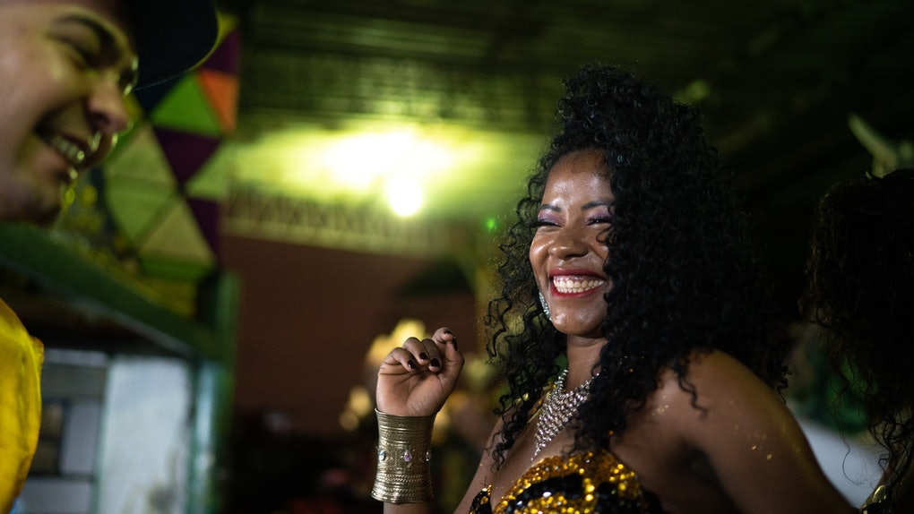 A woman smiles and dances in her Mardi Gras outfit.