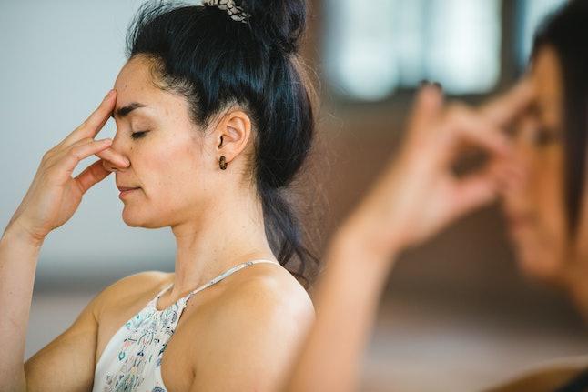 Women practice pranayama breathing, a type of breathwork