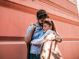 A happy couple embraces while exploring a city.