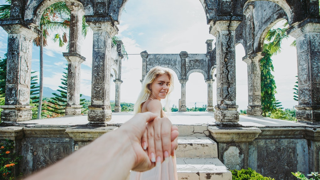 A couple holds hands while walking through ruins in Bali on a sunny day.