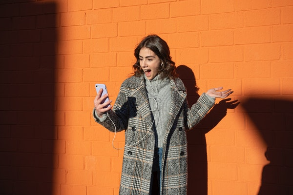 A fashionable woman smiles while standing in front of an orange wall and taking a selfie on her phone.