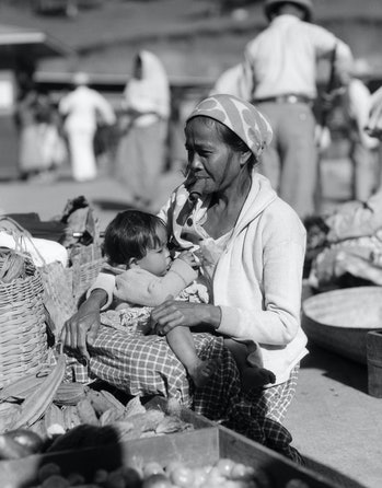 1920s 1930s WOMAN MOTHER SITTING SMOKING CIGAR CHEROOT HOLDING BABY CHILD IN MARKET PLACE BAGUIO PHILIPPINES