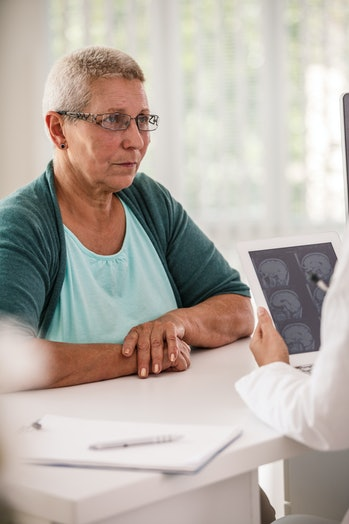 Woman listening to doctor explaining MRI test results - stock photo