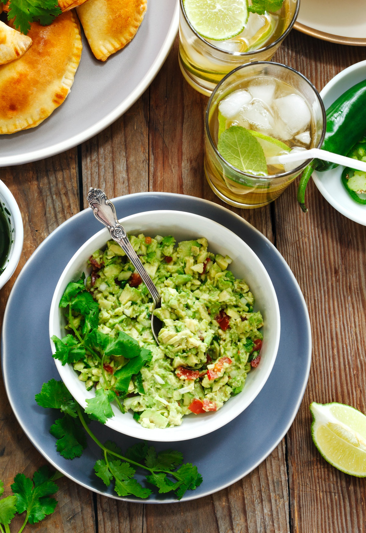 A bowl of guacamole sits on a wood table next to other vegan foods.