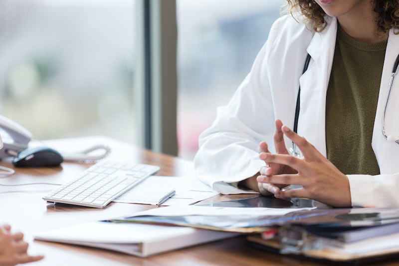 A doctor at their office. Being body-shamed at the doctor's is a common experience for people of a higher weight, and it can get in the way of effective medical care.