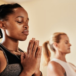 A person sits with her eyes closed in a meditative yoga pose. Meditation before or after a workout c...