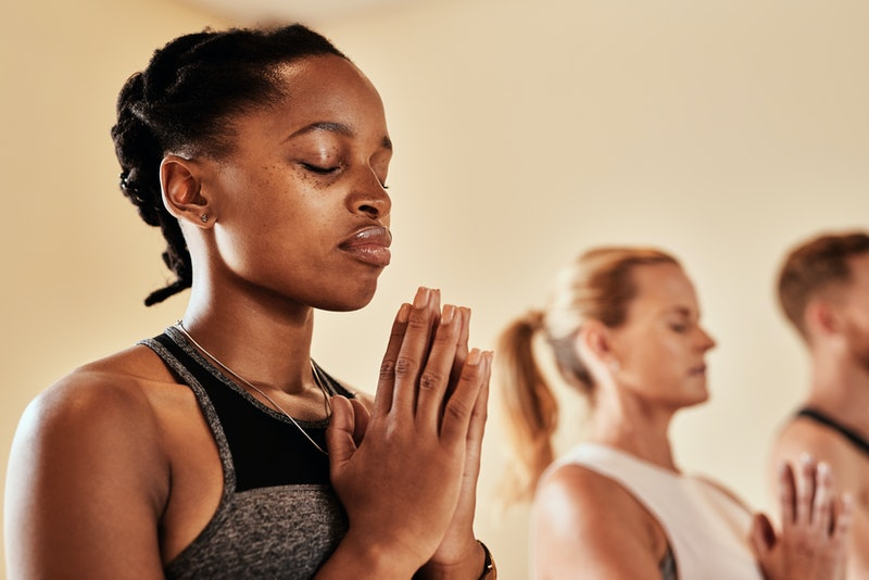 A person sits with her eyes closed in a meditative yoga pose. Meditation can help boost the quality of your workout, experts say.
