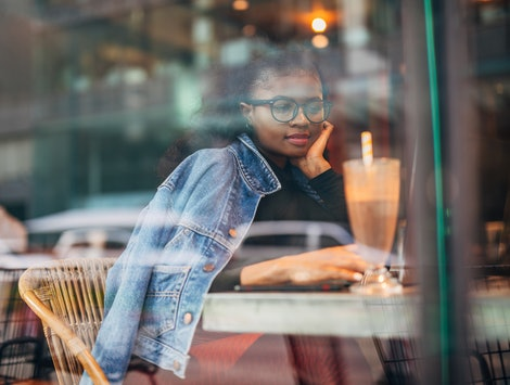 A woman sits inside a cafe. Experts reveal what happens to your body when you stop being vegetarian