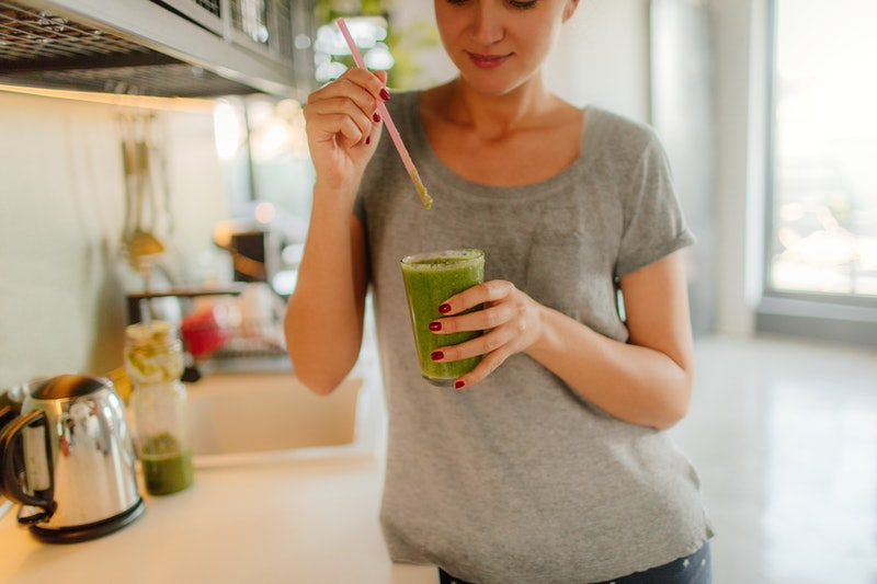 A woman fixes herself a green smoothie in her kitchen. Intuitive eating is touted as a way to fix relationships with eating, but it doesn't always work that simply