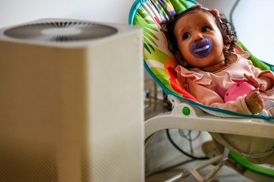 baby next to an air purifier