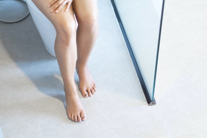 A woman sits on the toilet. Passing gas without any scent is one way your farts are trying to give y...