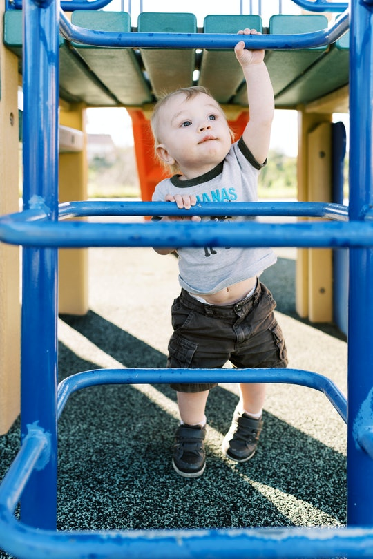 a toddler boy climbing up a jungle gym