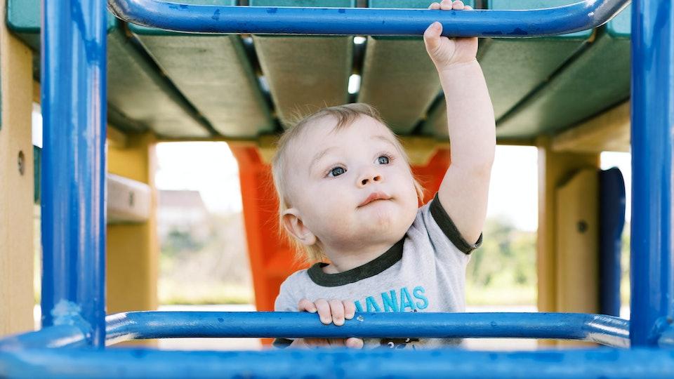 a toddler boy climbing up a jungle gym