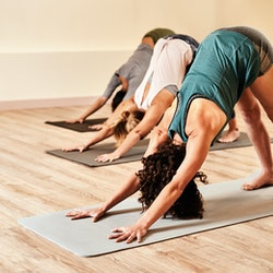 Three women in downward dog yoga pose, known to make people fart. Why do some farts smell like eggs? Here's what the different kinds of farts mean