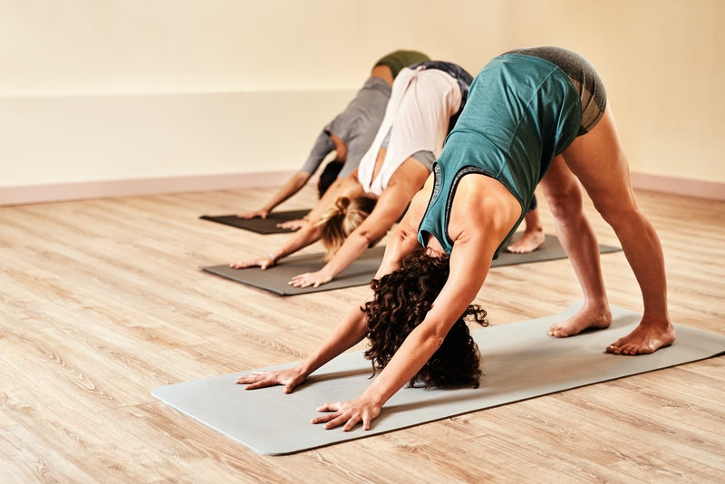 Three women in downward dog yoga pose, known to make people fart. Why do some farts smell like eggs?...