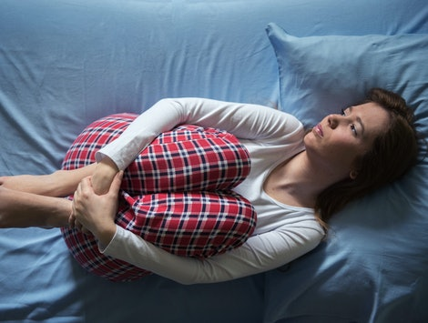 A woman is curled up in bed. Missing periods can be a sign of medical issues or problems like intense stress.
