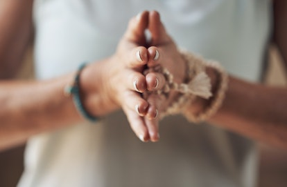 A person brings their palms together in front of their chest. Integrating mindfulness into your workout through techniques like breathwork and visualization can enhance the quality of your workout.