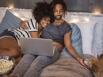 man woman in bed eating popcorn with laptop