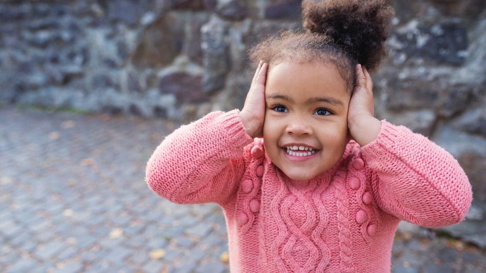 toddler girl covering her ears